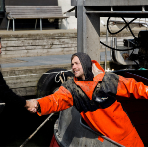 Handshake between fisherman and person, signifying a new relationship in the fishing industry